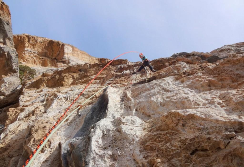 Utilisation d'une corde de hissage (rouge) en plus de la corde d'assurage à simple (verte) dans une longueur déversante. La corde de hissage (rouge) est attachée au grimpeur et va directement jusqu'au relais où elle est passée dans une dégaine.